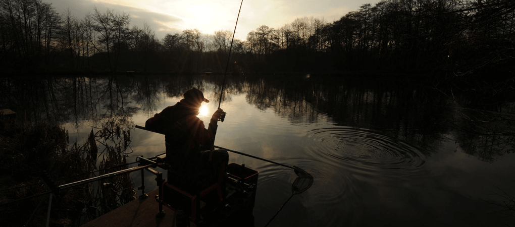 man-sitting-fishing-in-lake-during-sunset